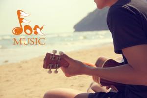 Teen playing Ukulele on beach