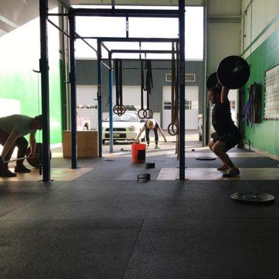 gym members working out in squat racks