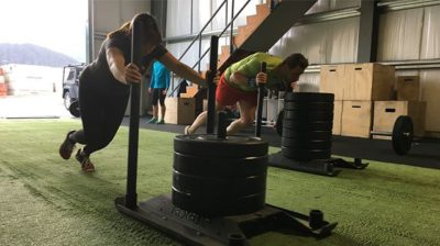 Tongass Fitness members pushing weight sleds across turf