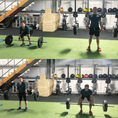 man and woman dead lifting in front of cardio machines