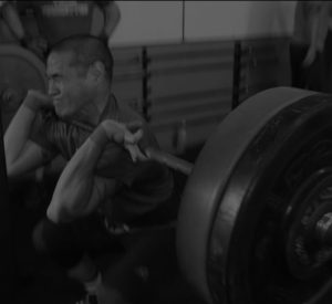 Man squats with barbell