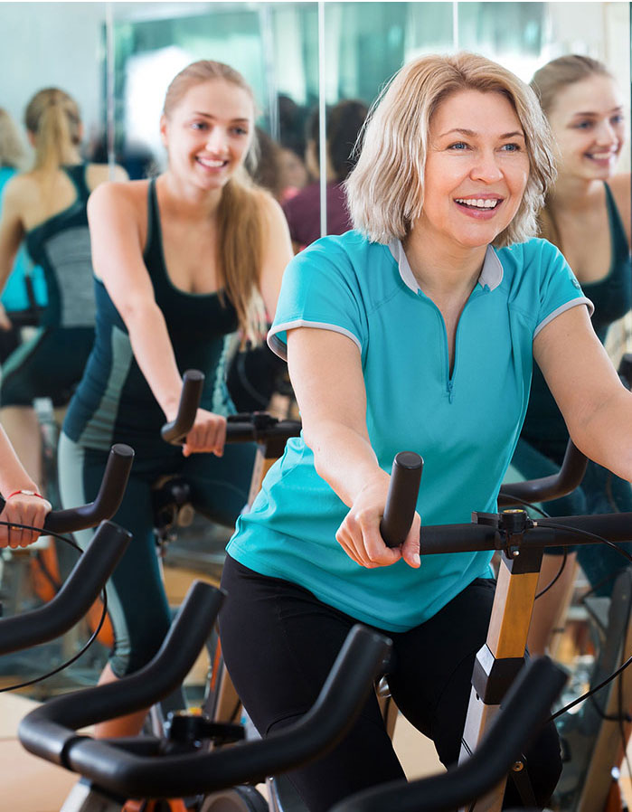 women at the gym on the bycicle equipment