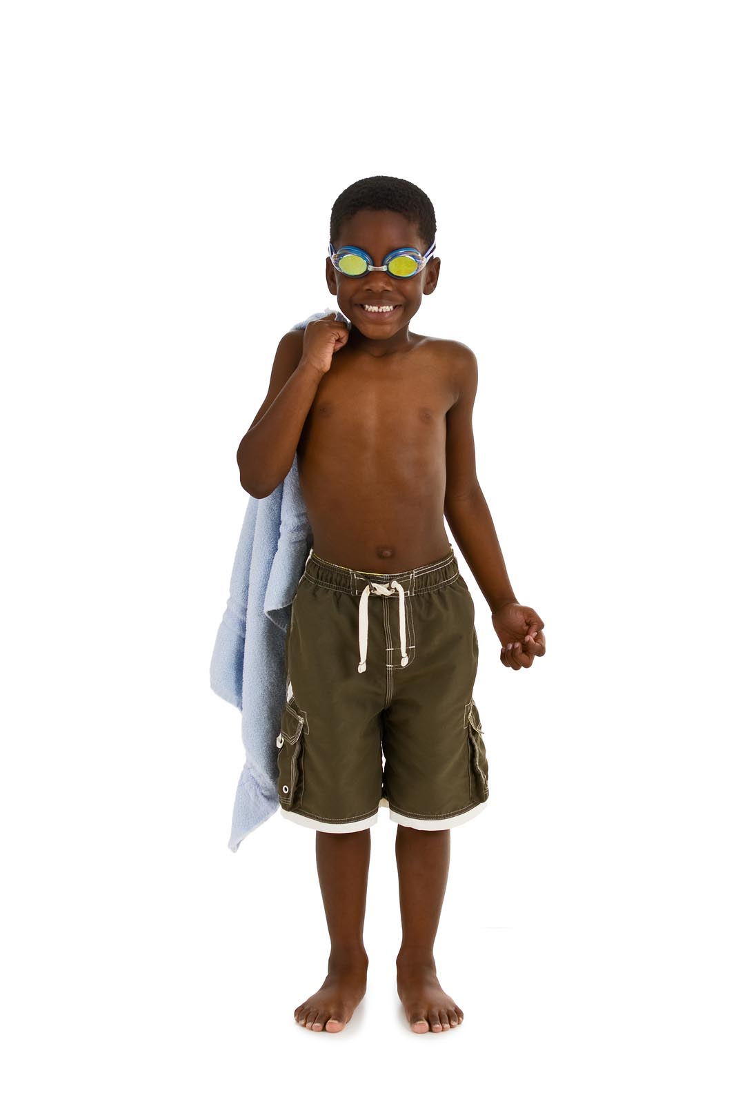 A young African American boy wearing swim trunks and goggles and carrying a towel. Isolated on a white background.
