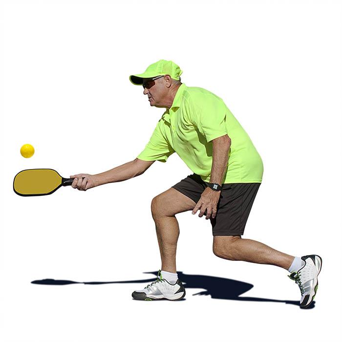 senior man hitting a forehand stroke during pickleball match.