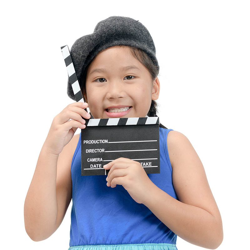 Little Director holding clapper board or slate film for making video cinema isolated on white background