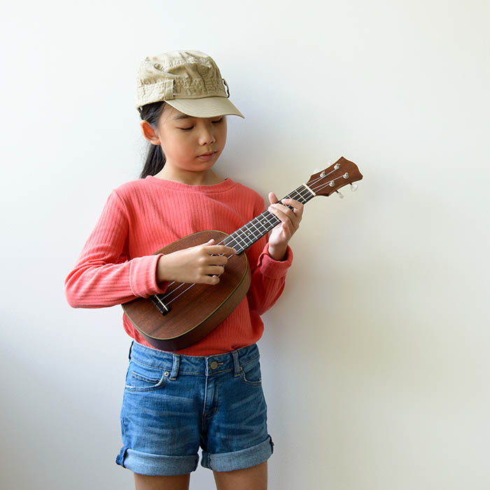 a young asian girl play an instrument