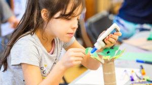 a Child glueing together artwork