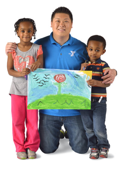 YMCA child care worker with two children holding artwork