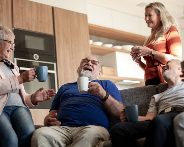 group of seniors in room drinking coffee and laughing