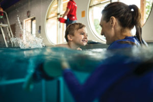 boy at swim lesson in water with instructor