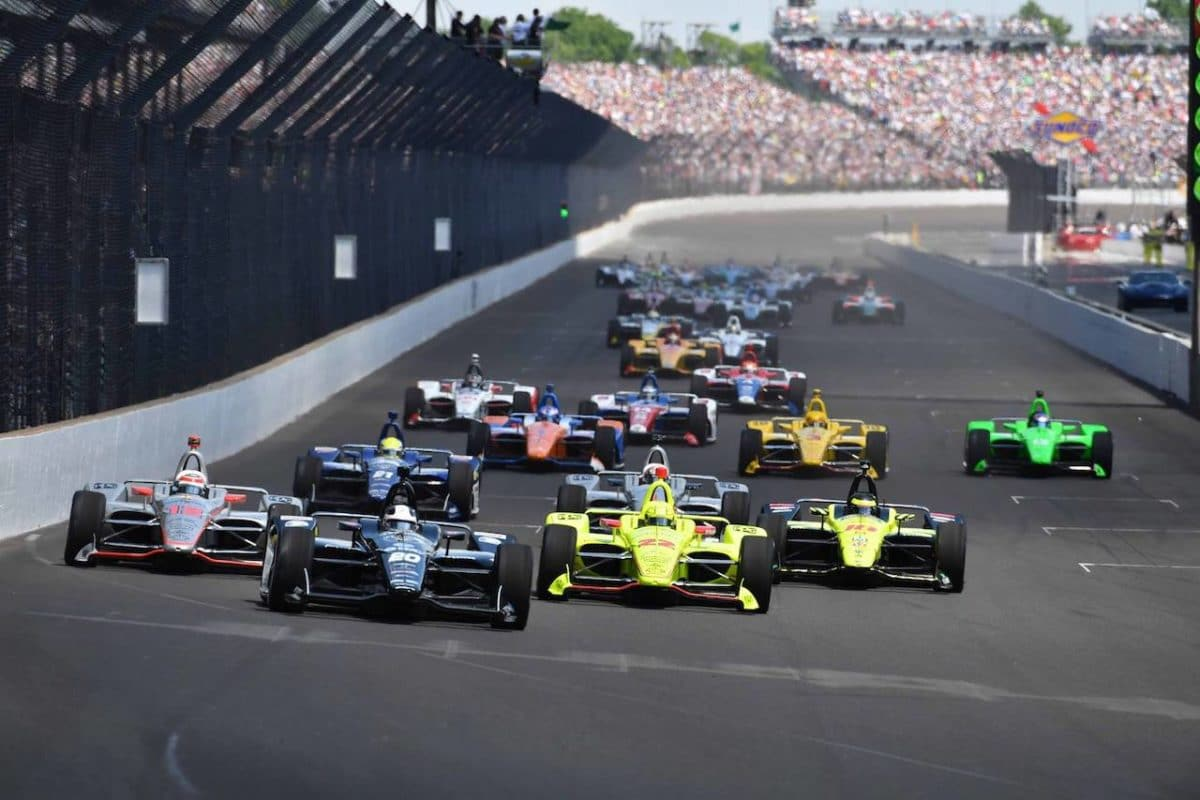 Indy 500 cars racing around track with crowd in background