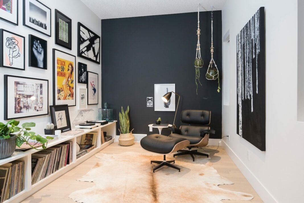 living room with black wall, pictures on wall, and records on floor shelf