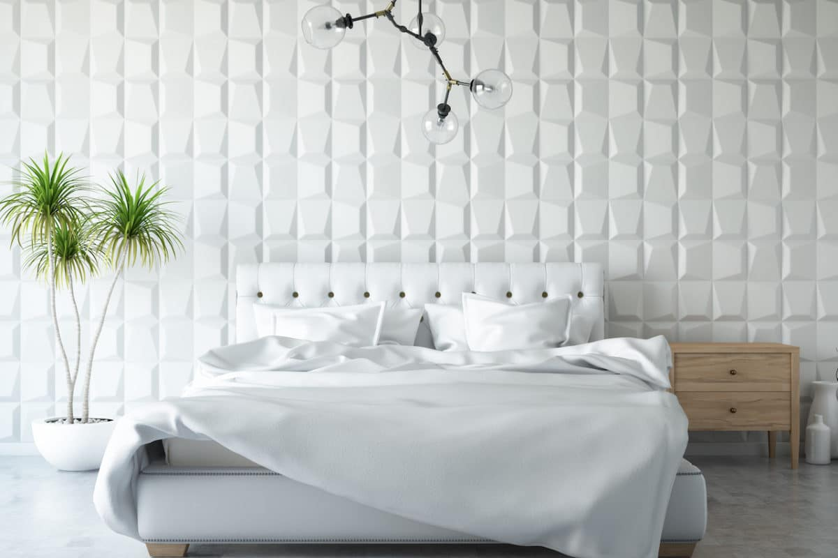white bed in white room with green potted plant next to it