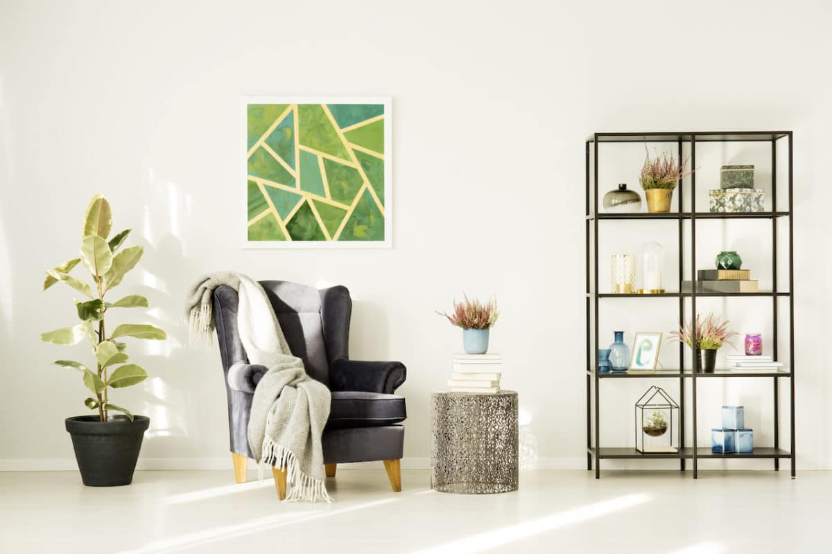 living room with brightly colored painting, bookshelf, chair, and decorations