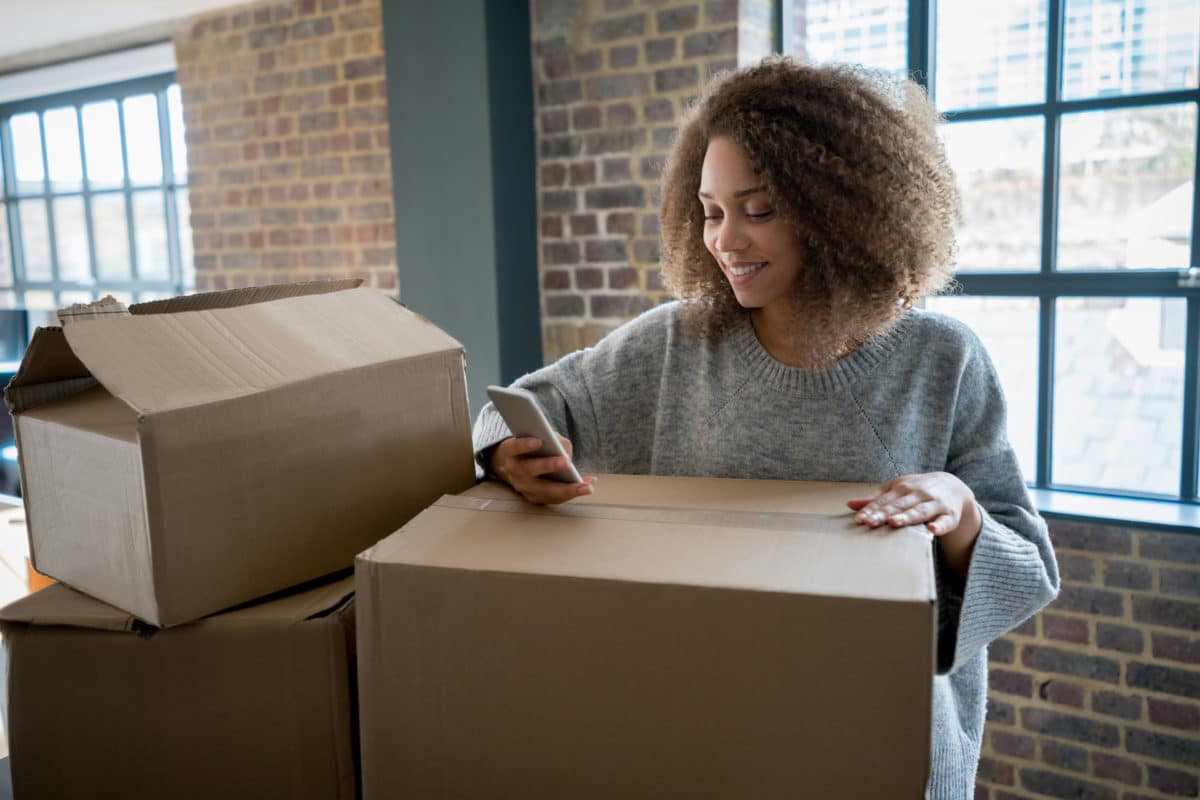 woman on her phone smiling while resting arm on moving box