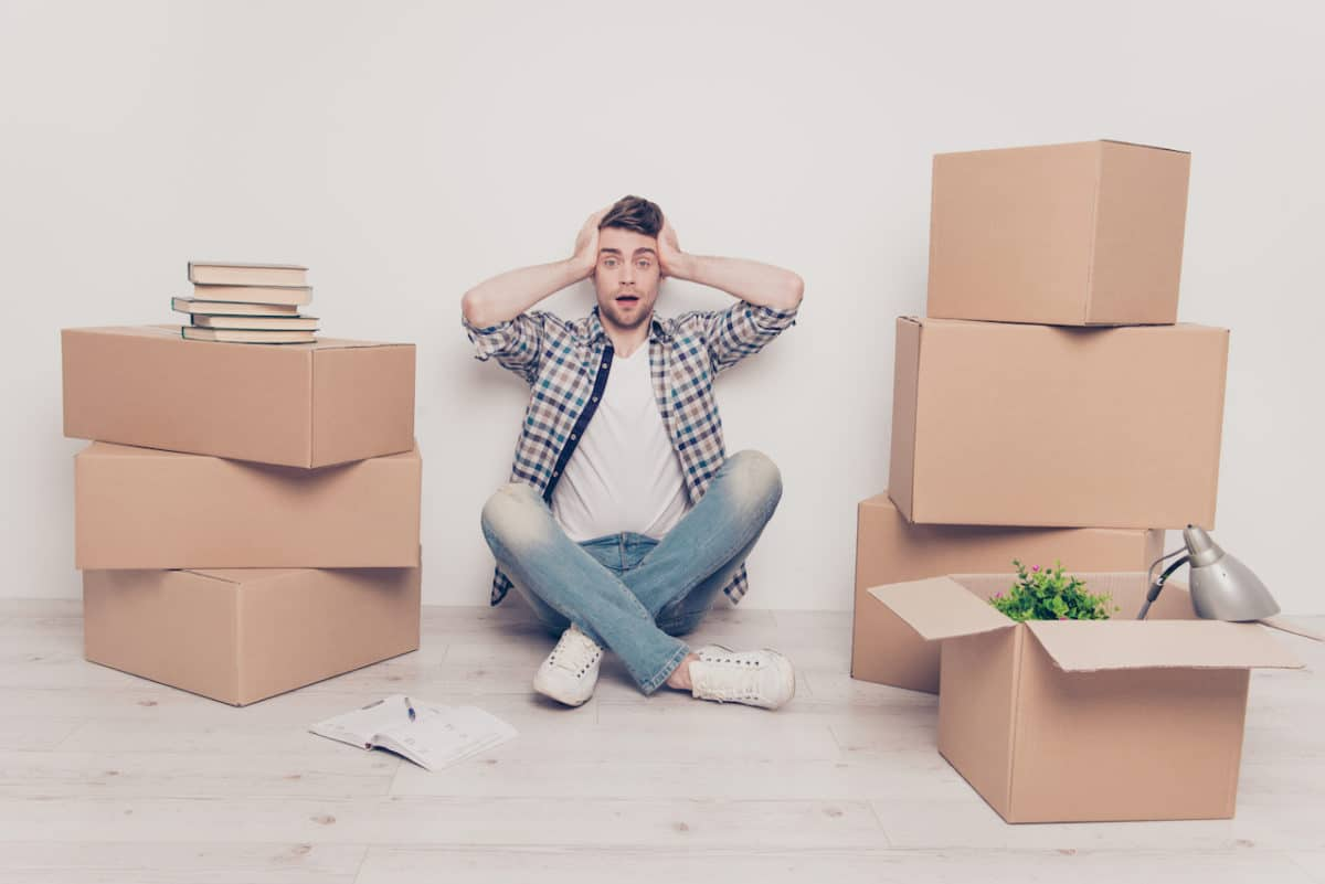 boy sitting on ground with hands on head looking overwhelmed next to moving boxes