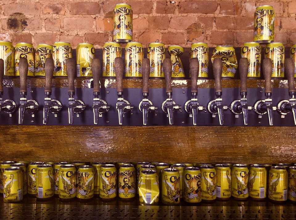 beer taps on wall and beer cans above and below them at bar