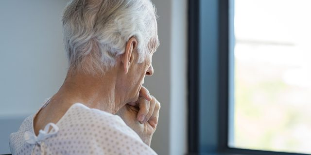 Lonely senior man in hospital looking out of window