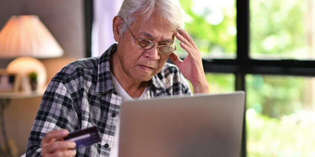 Senior man using laptop to pay bills