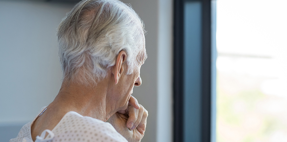 Senior man in health care setting gazing out window