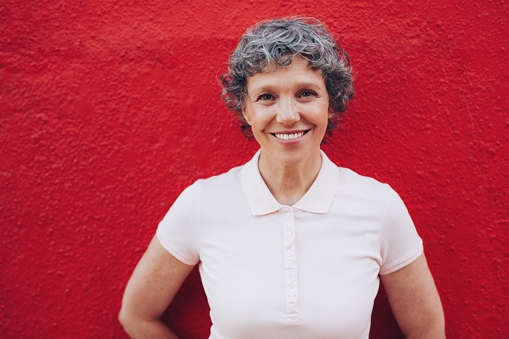 Smiling woman in front of red wall