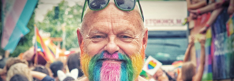 Older man at Pride with a rainbow-coloured beard