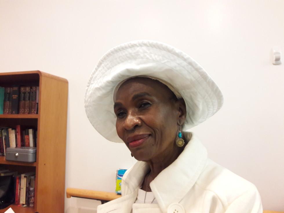 Senior woman smiling, wearing a white hat