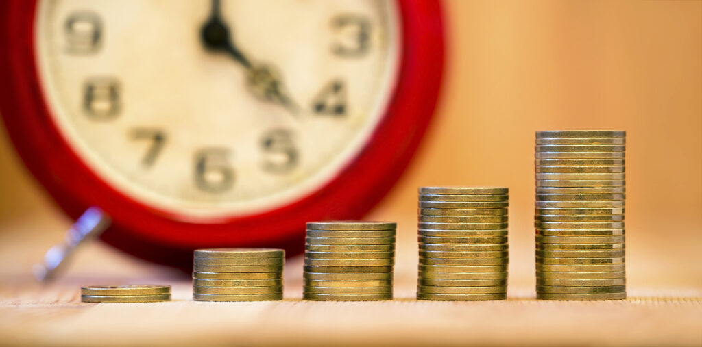 Stacks of loonies resembling a bar graph in front of a clock