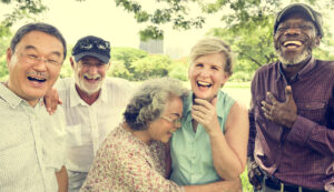Group of older adults laughing in the park