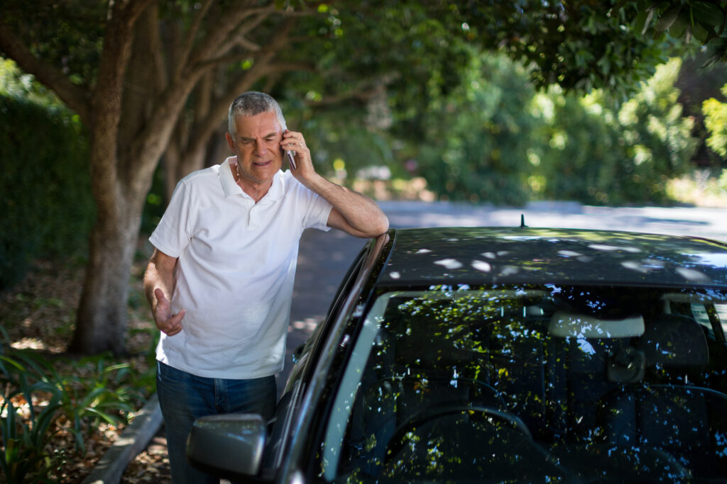 Older man standing next to car, making a phone call