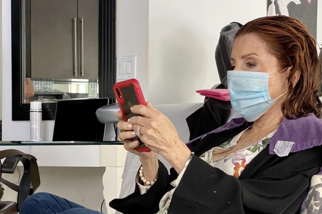 Older woman wearing mask and using smartphone