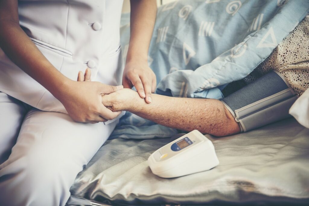 Nurse holding hand of older patient lying in hospital bed