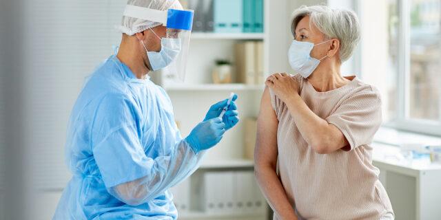 Older woman getting a flu shot from a nurse