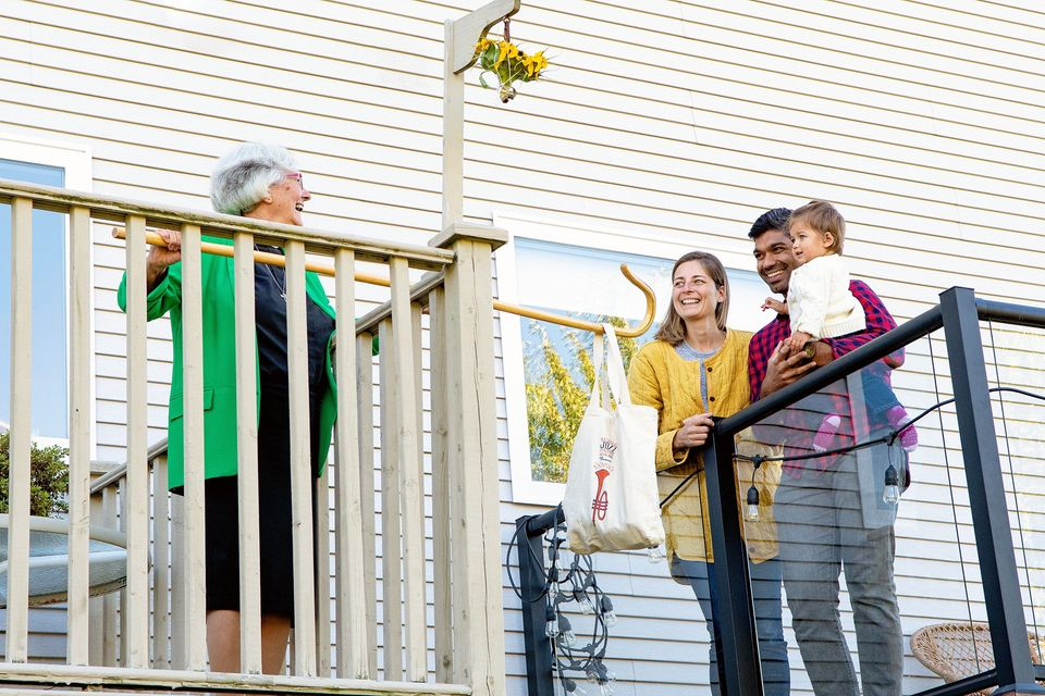 Reverend Dianne Parker, Board Member of the C.A.R.P. Nova Scotia Chapter, laughs with neighbours while standing on separate balconys