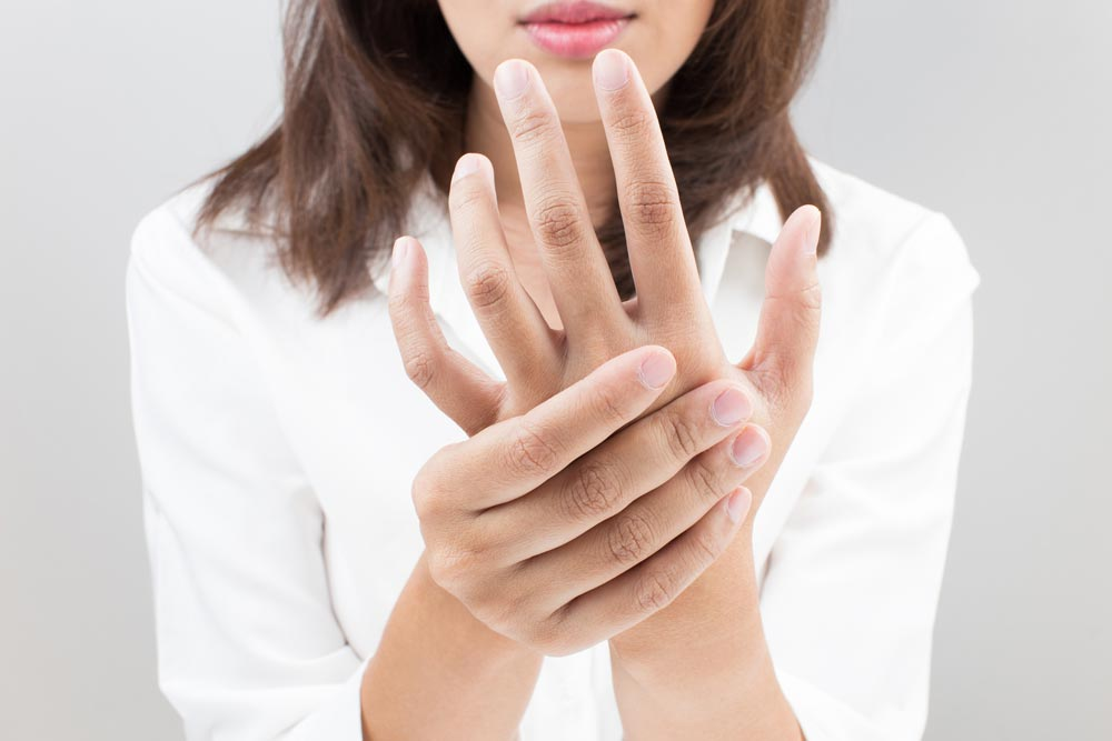 Woman suffering from arthritis, holding her hands.