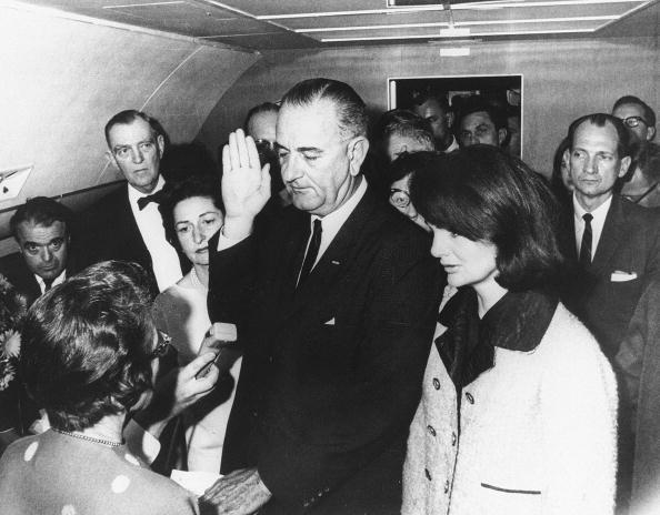 Flanked by Jackie Kennedy (R) and his wi
