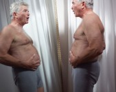 85484393-senior-man-examines-stomach-in-mirror-gettyimages