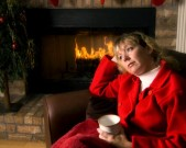 holidays-colette-thoughtful-woman-by-the-fireplace-at-gettyimages