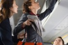 stewardess-assisting-passenger-with-luggage-gettyimages
