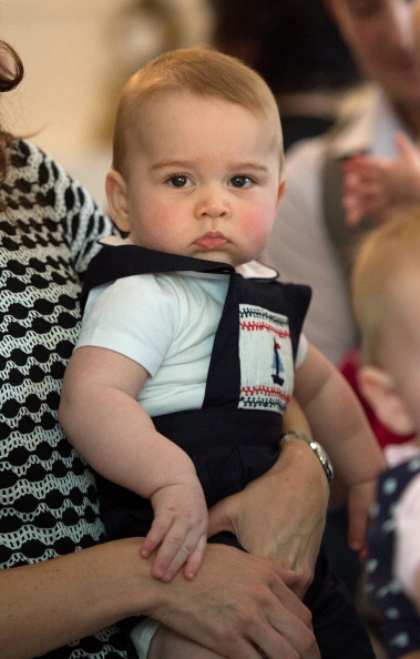 Catherine (L-out of frame), the Duchess of Cambridge, holds Prince George during a Plunket nurse and parents group visit at Government House in Wellington on April 9, 2014. Plunket is a national not-for-profit organisation that provides care for children and families in New Zealand. Britain's Prince William, Kate and their son Prince George are on a three-week tour of New Zealand and Australia.    AFP PHOTO / POOL / MARTY MELVILLE (Photo credit should read Marty Melville/AFP/Getty Images)