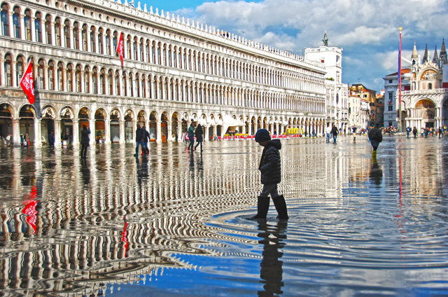 A boy wades through aqua alta in St. Mark's Square. This occurs when the tides rise to the point they breach Venice's shoreline.