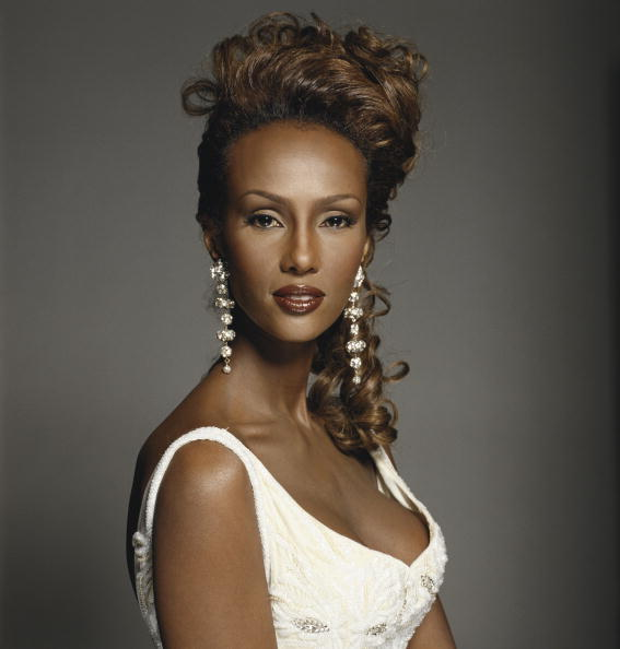 Somalian supermodel Iman, wearing long earrings and a white dress, 1994. (Photo by Terry O'Neill/Getty Images)