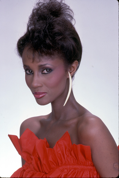 Portrait of Somali-born American fashion model Iman, dressed in red ruffled, strapless top, as she poses against a white background, New York, New York, 1981. (Photo by Anthony Barboza/Getty Images)