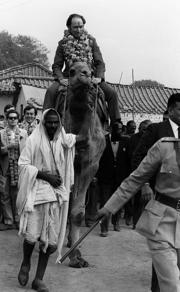 Prime Minister Pierre Trudeau, with a garland around his neck and a Hindu greeting symbol in paste on his forhead, rides a camel Jan 12, 1971 in the village of Benares, India, where he dedicated a well. (CP PHOTO/ Peter Bregg)