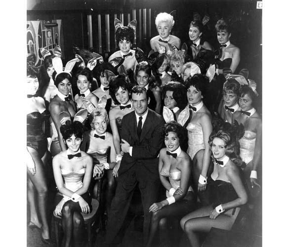 Playboy founder Hugh Hefner flanked by bunnies in one of his Playboy clubs, 1962