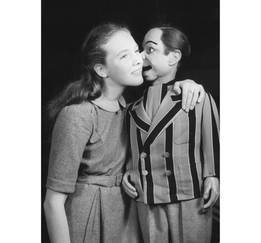 September 1950: Peter Brough's ventriloquist's dummy, schoolboy Archie Andrews, whispering into the ear of singer and film star Julie Andrews. (Photo by George Konig/Keystone Features/Getty Images)