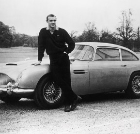 ca. 1964 --- Actor Sean Connery, the original James Bond, is pictured here on the set of Goldfinger with one of the fictional spy's cars, a 1964 Aston Martin DB5. --- Image by © Corbis