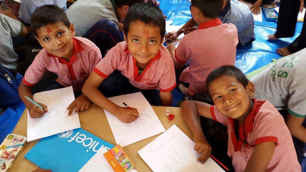 A group of boys begin their studies again at the Kuleshwor School in Kathmandu, Nepal with drawings. Children like these at the Kuleshwor School in Kathmandu, Nepal are happy to finally be back to school for the first time this morning since the first of two Nepal earthquakes which occurred on 25 April 2015. Their school was heavily damaged and is not safe to enter so the children have returned to class in temporary learning spaces built with UNICEF support. UNICEF also provided education and recreation kits for the children, along with psycho-social training for teachers – and continues to support damage assessment of schools damaged in the two Nepal Earthquakes. Back to School for first time in Nepal since first Earthquake Photos Kent Page 2015