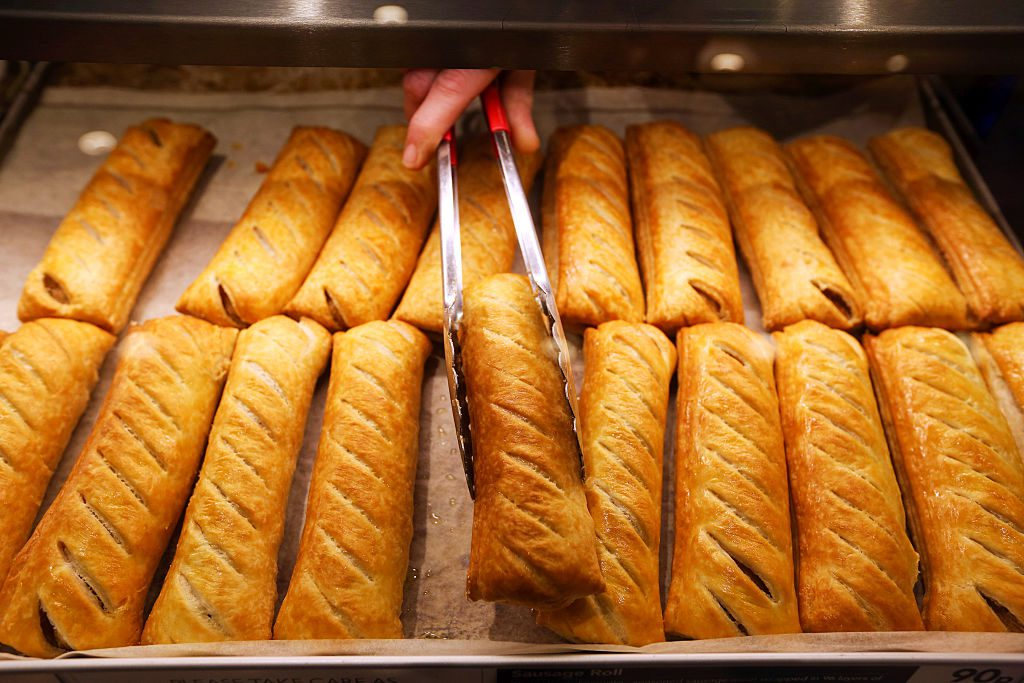 An employee uses tongs to remove a sausage roll from the counter in a Greggs Plc sandwich chain outlet in Caterham, U.K., on Thursday, Oct. 22, 2015. Same-store sales at Greggs have grown 5.6 percent so far in 2015, up from 3.9 percent across the same period last year, and the company said on Oct. 6 that full-year growth will exceed its previous forecast slightly. Photographer: Chris Ratcliffe/Bloomberg via Getty Images