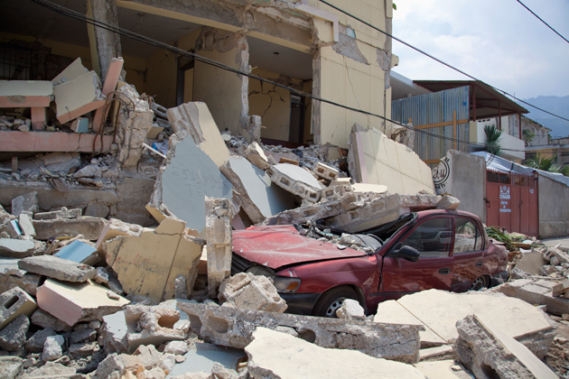 A car is crushed when a building collapses after the earthquake